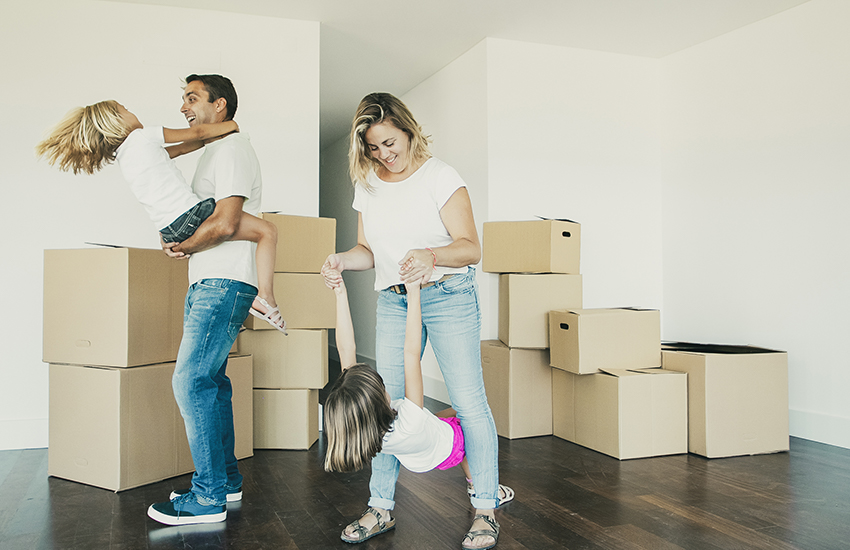 Photo of a couple and their two children dancing in an empty living room with moving boxes.