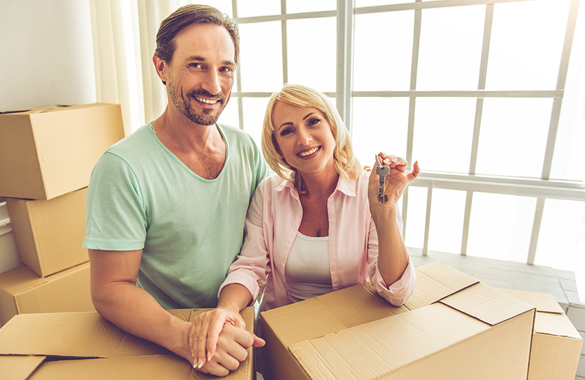 Photo of middle-aged couple moving into new house with moving boxes.